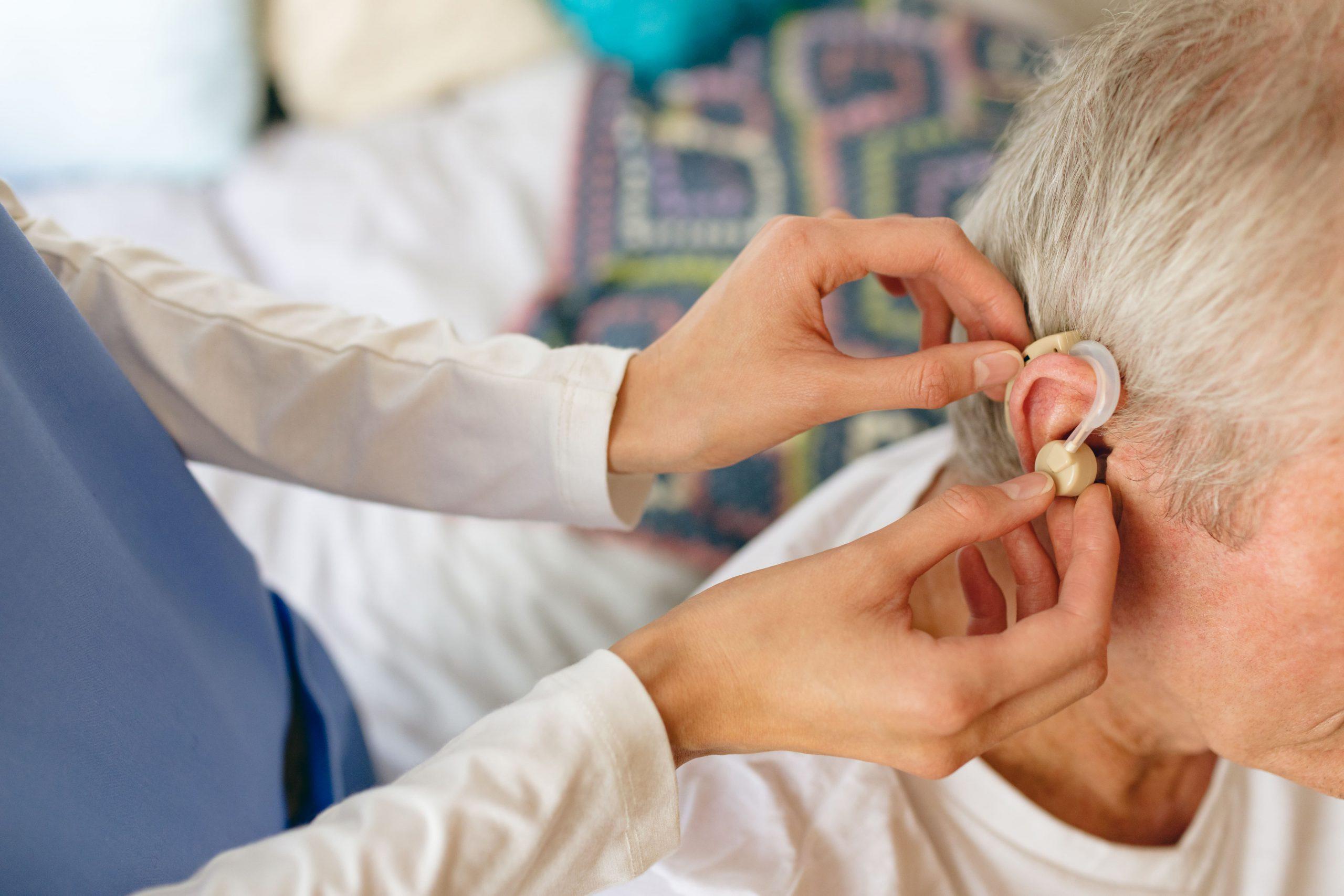 man krijgt hulp met zijn oorapparaat